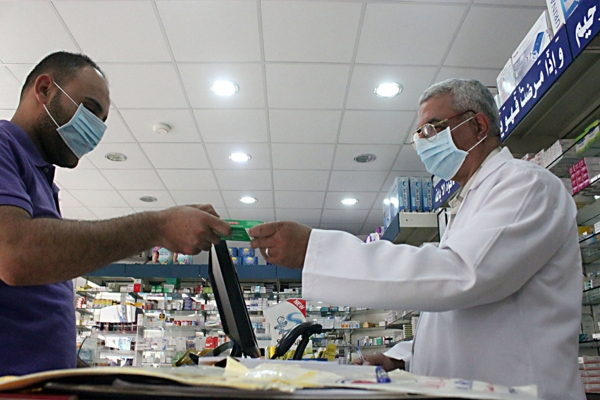 A man, wearing a surgical mask as a precautionary measure against the novel coronavirus, pays for medicine at a hospital pharmacy in Khobar city in Dammam May 21, 2013. Saudi Arabia has reported another case of infection in a concentrated outbreak of a new strain of a virus that emerged in the Middle East last year and spread into Europe, the World Health Organization (WHO) said on May 18, 2013. In a disease outbreak update issued from its Geneva headquarters, the WHO said the latest patient is an 81-year-old woman with multiple medical conditions. She became ill on April 28 and is in a critical but stable condition. Worldwide, there have now been 41 laboratory-confirmed infections, including 20 deaths, since the new coronavirus was identified by scientists in September 2012. REUTERS/Stringer (SAUDI ARABIA - Tags: HEALTH SOCIETY)
