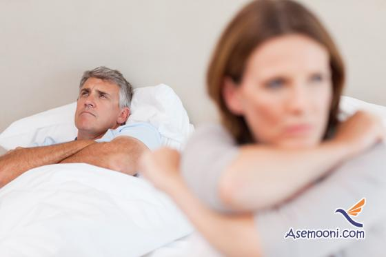 Sad man in bed with his wife in the foreground