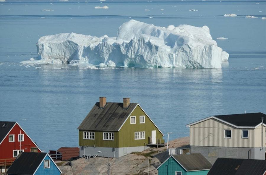 یک کوه یخی از مقابل خانههای مردم منطقه خلیج دیسکودر گرینلند