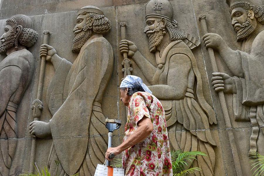 عبور یک زن پارسی هندی از مقابل معبد پارسیان هندی در شهر بمبئی هند
