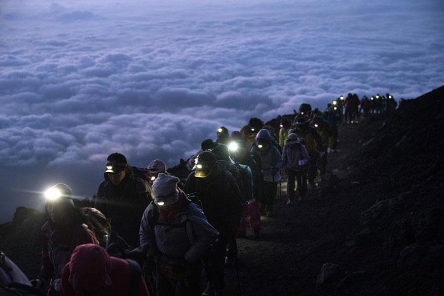گروهی از کوهنوردان در حال صعود به قله کوه فوجی در ژاپن
