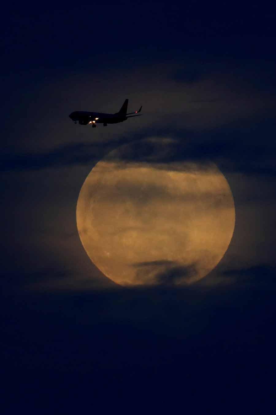 یک فروند هواپیمای تجاری در حال پرواز قبل از شروع کسوف کامل ماه در کالیفرنیا