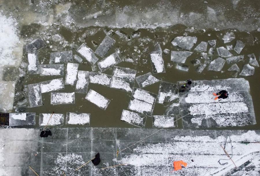 شکستن قطعههای یخ از رودخانه  سونگ هوا در چین برای استفاده در جشنواره سازههای یخی در هاربین چین