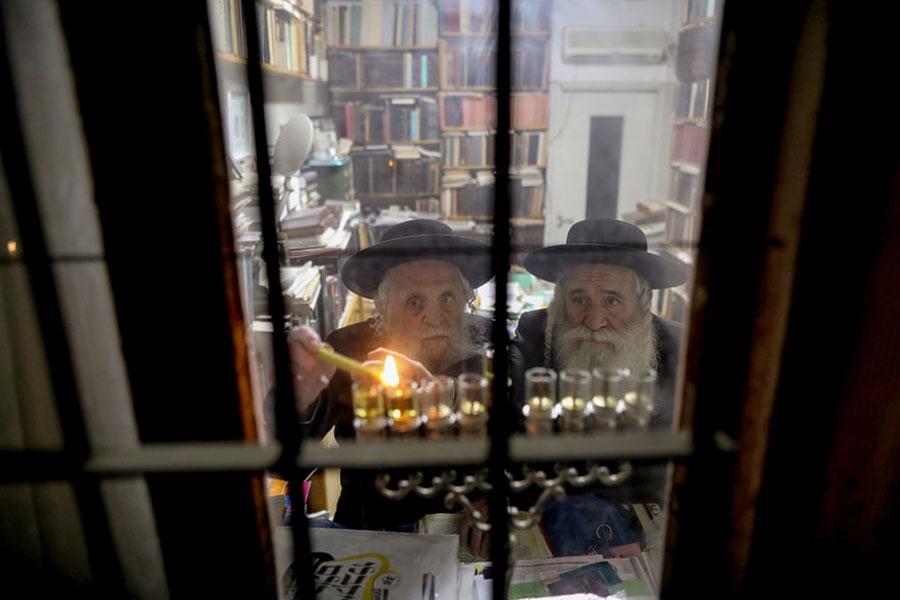 روشن کردن شمع از سوی یهودیان در عید حنوکا در شهر قدس