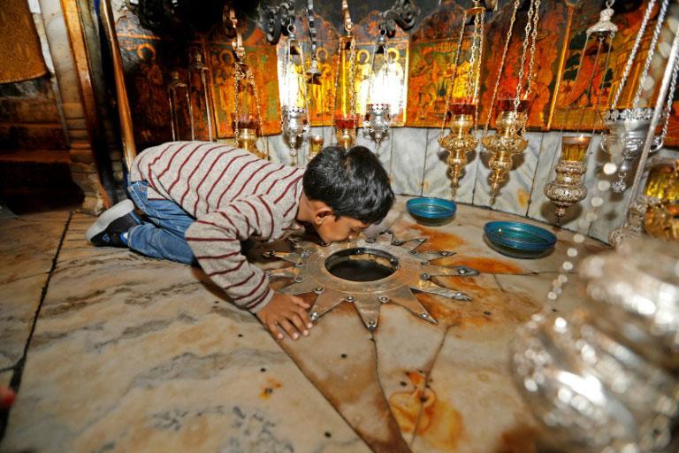بوسه یک زائر مسیحی بر محل تولد عیسی مسیح در کلیسای مهد در بیت لحم فلسطین