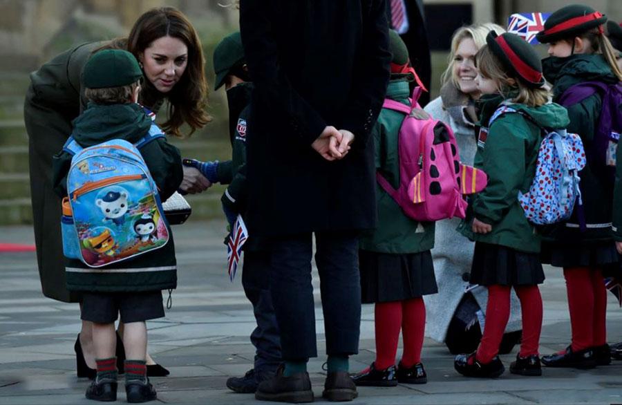 کیت همسر شاهزاده ویلیام بریتانیا در حاشیه یک مراسم عمومی با چند کودک دانش آموز خوشوبش میکند.