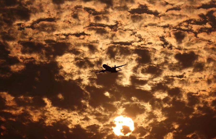 نمایی از پرواز یک هواپیما در هوای ابری و غروب شهر احمدآباد هند