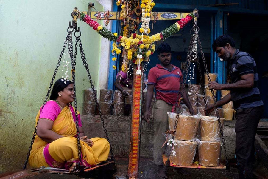 زن هندو به اندازه وزن خود شکر قهوهای برای پیشکش و نذر خریداری میکند