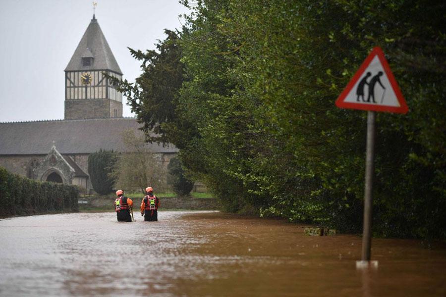 ماموران آتش نشانی در حال اندازه گیری عمق سیلاب انگلیس