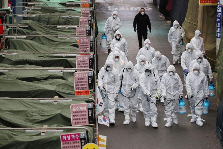 کارگران فروشگاهی با لباس مخصوص درحال ضدعفونی کردن محل