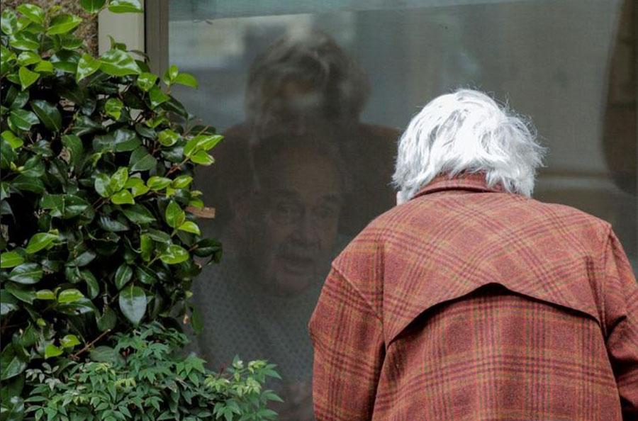 عیادت از پشت شیشه همسر از شوهر کرونایی در یک مرکز درمانی در شهر کرکلند ایالت واشنگتن آمریکا