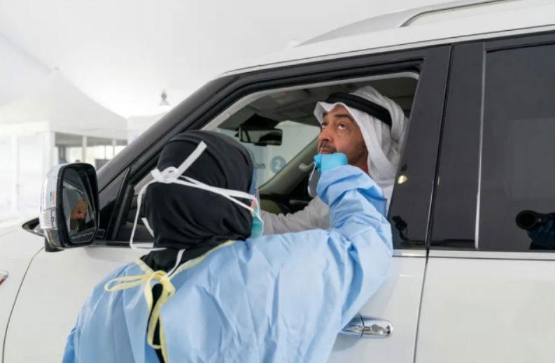 شیخ محمد بن زاید آل نهیان ولیعهد ابوظبی در حال دادن تست کرونا از داخل اتومبیل خود در یک مرکز سیار تست کرونا در شهر ابوظبی
