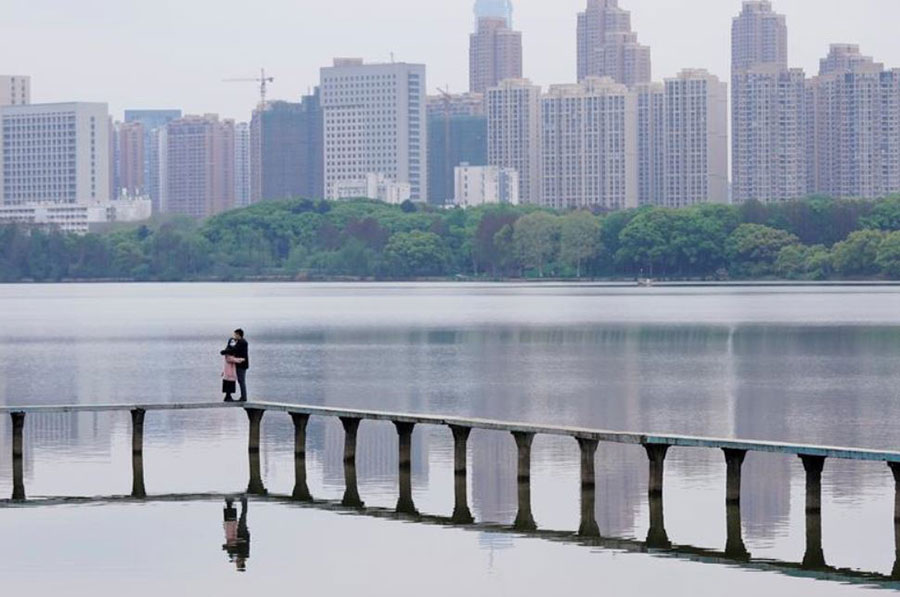 بازگشت آرام وضعیت عادی در شهر ووهان چین. یک زوج چینی در کناره دریاچه شرقی شهر ووهان