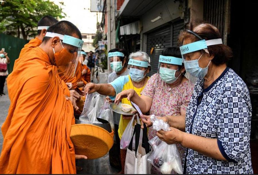 راهبان بودایی در بانکوک تایلند با رعایت تمام موارد ایمنی کرونایی در حال جمعآوری نذورات مردمی