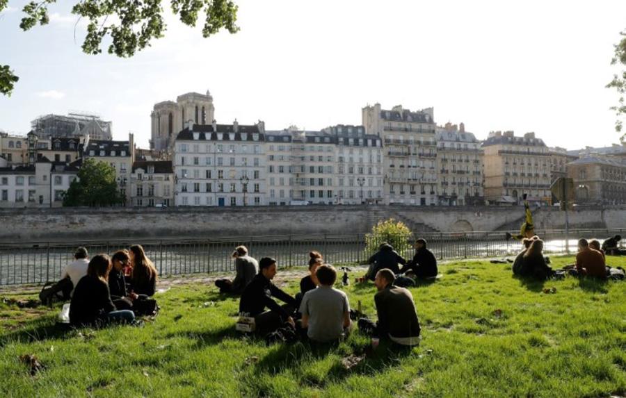 پس از برداشته شدن محدودیتهای قرنطینه خانگی، گروهی از مردم پاریس در دستههای 3-4 نفری، در حاشیه رود سن روی چمن نشسته و در حال آفتاب گرفتن در هوای بهاری هستند