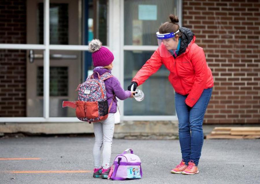 ضدعفونی کردن دستهای دانشآموز در حیاط مدرسه
