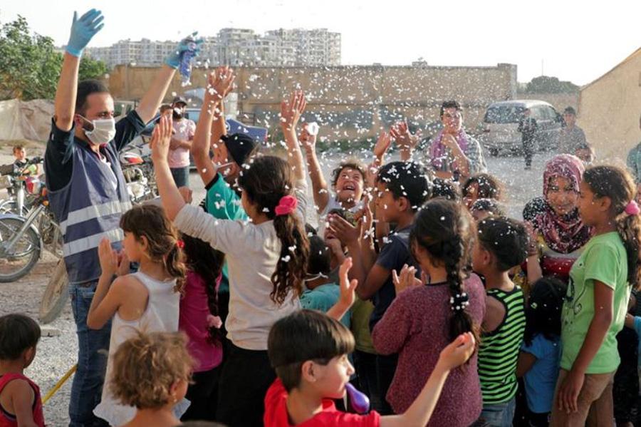 یک نیروی داوطلب انجمن بینالمللی امداد و توسعه (ONSUR) پیش از تعطیلات عید فطر در حال سرگرم کردن کودکان در اردوگاه آوارگان در استان ادلب سوریه