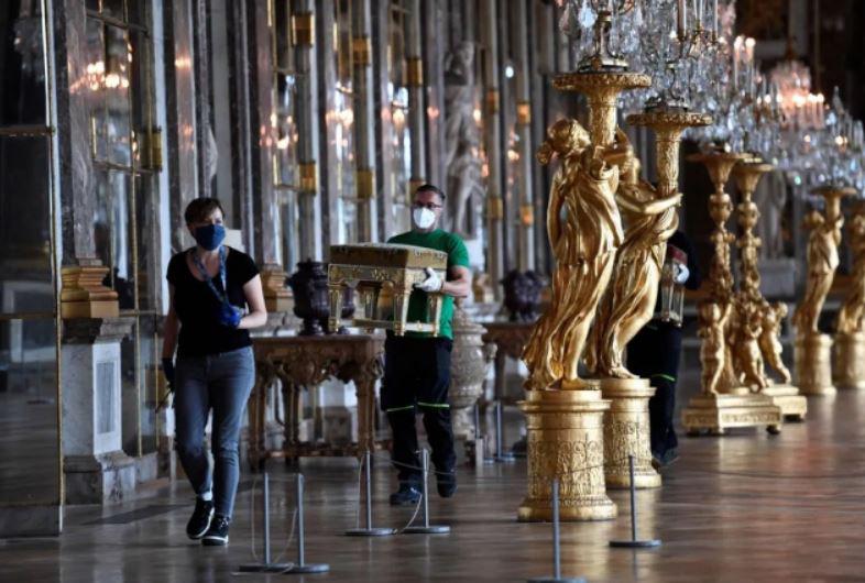 یک کارمند در حال حمل مبلمان در تالار آینه کاخ ورسای فرانسه در پی بازگشایی پس از تعطیلی 82 روزه این کاخ موزه در پی بحران شیوع کرونا