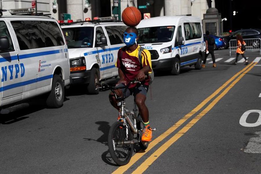 معترض ضدنژادپرستی در شهر نیویورک آمریکا در حال نمایش خیابانی با توپ بسکتبال