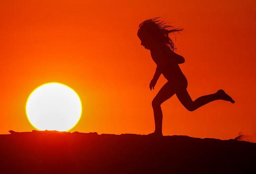 دویدن یک کودک در غروب ساحل ایالت کالیفرنیا آمریکا