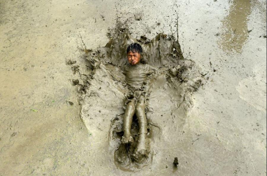 بازی در گِل و لای شالیزارهای برنج در حومه شهر کاتماندو نپال در جشنواره روز ملی برنج