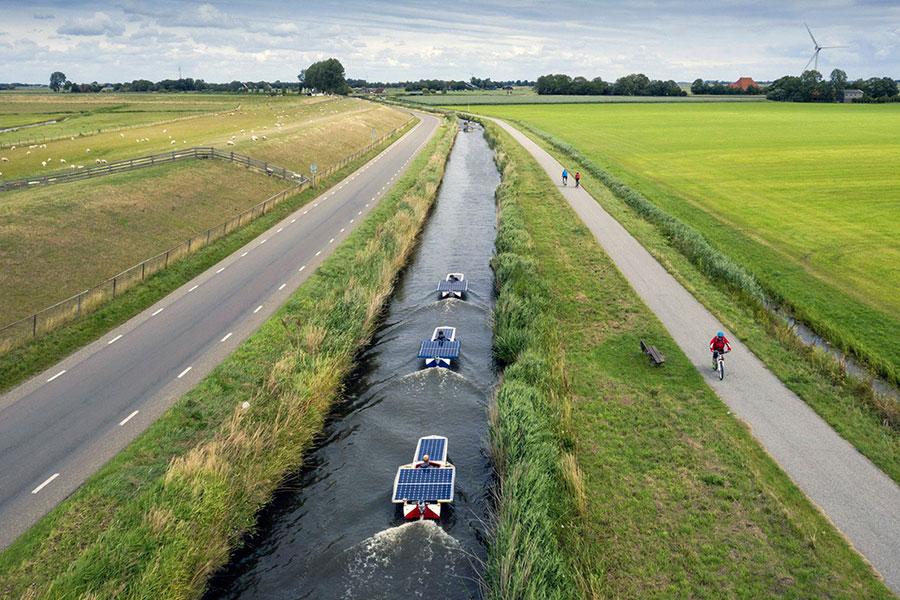 یک تصویر هوایی از دانش آموزانی که با قایق های خورشیدی در امتداد Elfstedentocht در Hindeloopen، هلند قایقرانی می کنند